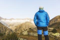 Alpinist стоит во время рассвета рассвета перед горными вершинами Стоковое Изображение