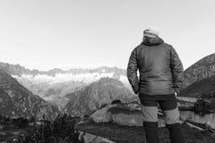 Alpinist стоит во время рассвета рассвета перед горными вершинами Стоковые Фото