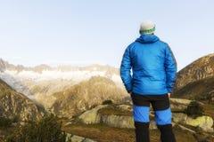 Alpinist стоит во время рассвета рассвета перед горными вершинами Стоковые Изображения RF