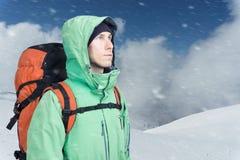 Alpinist человека смотрит вверх против ландшафта горы зимы Стоковые Фото