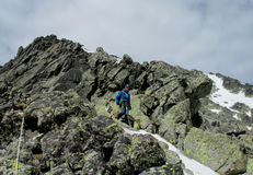 Alpinist, alpine climber walking to the top of the mountain through the snow and stones Royalty Free Stock Photos