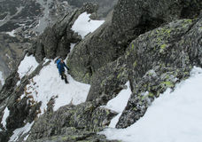 Alpinist, alpine climber walking to the top of the mountain through the snow and stones Royalty Free Stock Photography