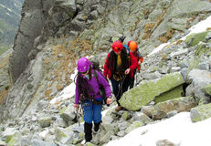 Alpinist, alpine climber walking to the top of the mountain through the snow and stones Royalty Free Stock Image