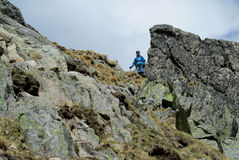 Alpinist, alpine climber walking to the top of the mountain through the snow and stones Stock Photos