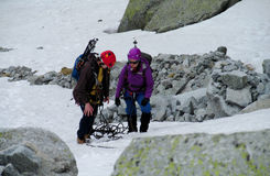 Alpinist, alpine climber walking to the top of the mountain through the snow and stones Royalty Free Stock Photo