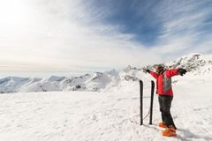 Alpinist with back country ski. Male adult alpinist with pair of back country ski on the mountain summit. Shot in backlight, stunning panoramic view of the Royalty Free Stock Photo