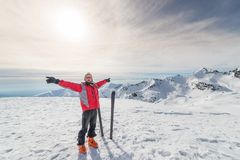 Alpinist with back country ski. Male alpinist with arms outstretched near pair of back country ski on the mountain summit. Shot in backlight, stunning panoramic Stock Photos