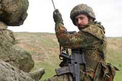 alpinist beväpnat hängande militärt rep Arkivfoton