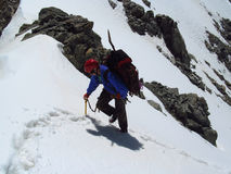 An alpinist climber walking on the top of the mountain through the snow Stock Images