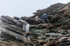 Alpinist im extrem gefährlichen gefrorenen felsigen Abschnitt, im Risiko und in der Gefahr im Hochgebirge, Alpen, Frankreich stockbild
