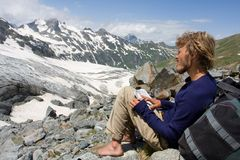 Alpinist looking to map in wild mountains. Barefoot alpinist sitting on rock and looking to map in wild mountains Royalty Free Stock Image