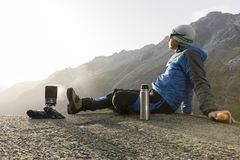 Alpinist makes a break in the mountains and cooks tea Stock Photos
