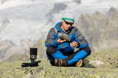 Alpinist makes a break in the mountains and pours a tea Royalty Free Stock Image