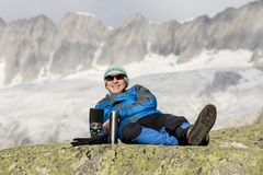 Alpinist makes a tea break before breathtaking mountain views Royalty Free Stock Photos