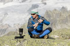 Alpinist makes a tea break before breathtaking mountain views Royalty Free Stock Photography