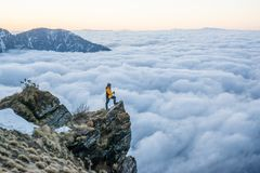 Alpinist Man Standing At The Edge Of The Cliff At Mountains Dressed In Warm Clothes And Backpack Stock Photography