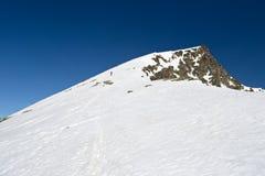 Alpinist in mot toppmötet Arkivbild