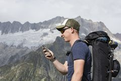 Alpinist is oriented with a GPS device in the terrain. Swiss alps Stock Images