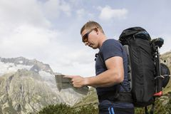 Alpinist is oriented with a map on the terrain Stock Image