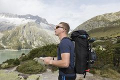 Alpinist is oriented with a map on the terrain. In the Swiss alps Stock Photography