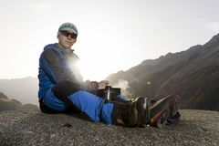 Alpinist pauses and prepares a warm drink, Switzerland Royalty Free Stock Photos