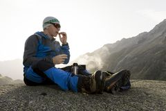 Alpinist pauses during the sunrise and prepares a hot tea Royalty Free Stock Photography
