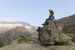Alpinist sits on a rock and enjoys the view. Switzerland Royalty Free Stock Photos