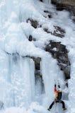 Alpinist som klättrar en icefall i Val D ` Aosta, Italien Arkivfoto