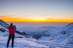 Alpinist som tar selfie på skymning på bergtoppmöte Arkivfoto