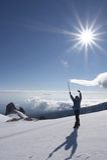 Alpinist and sun. Alpinist on the top of Sredniaya mountain. Kamchatka.  Russia Stock Photo