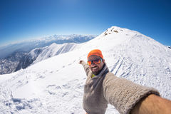 Alpinist taking selfie on snowcapped mountain, fisheye lens. Adult alpin skier with beard, sunglasses and hat, taking selfie on snowy slope in the beautiful royalty free stock photos