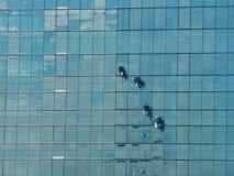 Alpinist vier, der für das Säubern des Gebäudefensterglases klettert Stockfotografie