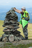 Alpinist woman making stone pile Royalty Free Stock Photos