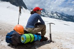 Alpinist woman sitting on her backpack Royalty Free Stock Images