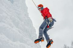 Alpinist Woman With Ice Tools Axe In Orange Helmet Climbing A Large Wall Of Ice. Outdoor Sports Portrait Stock Images