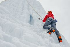 Alpinist Woman With Ice Tools Axe In Orange Helmet Climbing A Large Wall Of Ice. Outdoor Sports Portrait. Stock Photography