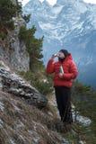 Alpinista al fondo dei picchi nevosi di inverno che riposa e che beve dalla tazza del metallo della boccetta di vuoto Immagine Stock