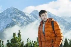Alpinista bello che posa al fondo roccioso nevoso sorprendente del paesaggio Fotografia Stock Libera da Diritti