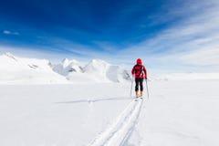 Alpinista che cammina su un ghiacciaio durante l'inverno ad alta altitudine e Fotografia Stock