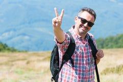 Alpinista che fa gesto di vittoria su sulla collina Fotografia Stock