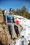 Alpinista che fa una pausa dall'alpinismo sulla montagna Immagine Stock