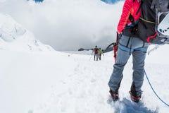 Alpinista che guarda giù il pendio Immagini Stock