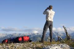 Alpinista che osserva attraverso i vetri di campo Immagini Stock Libere da Diritti
