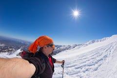 Alpinista che prende selfie sulla montagna snowcapped, fish-eye Immagini Stock