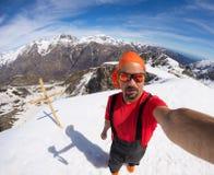 Alpinista che prende selfie sulla montagna snowcapped, fish-eye Immagine Stock