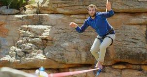 Alpinista che prova ad ottenere equilibrio sulla corda 4k archivi video