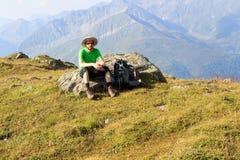 Alpinista che riposa sulla roccia davanti a panorama della montagna nelle alpi di Hohe Tauern Fotografie Stock