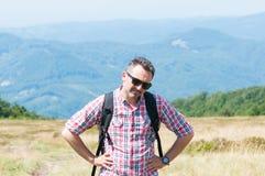 Alpinista che ritiene stanco dopo la scalata sulla cima Fotografia Stock Libera da Diritti