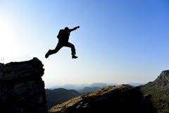 Alpinista che salta dalla roccia Fotografia Stock