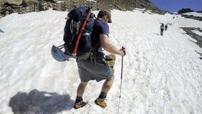 Alpinista che scala in salita dal lato soleggiato della montagna Immagine Stock